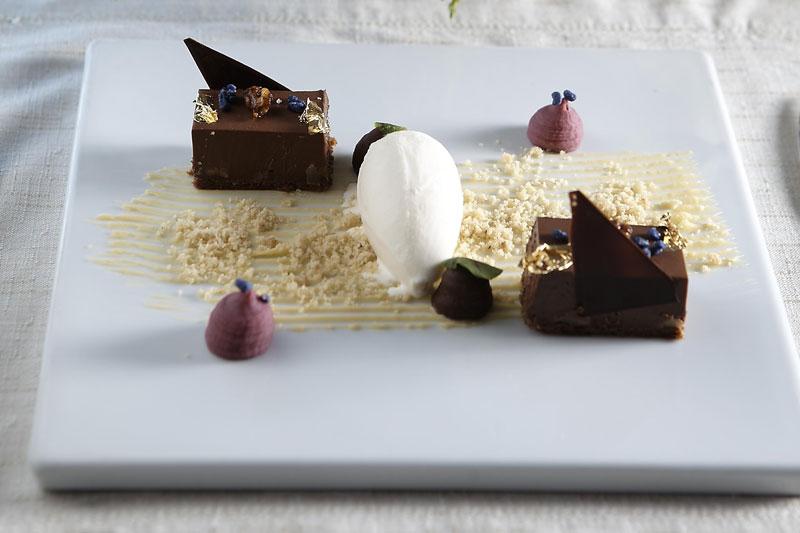 Σοκολατόπιτα με Valrhona bitter, καραμελωμένα καρύδια, παγωτό καϊμάκι και ζαχαρωμένες βιολέτες