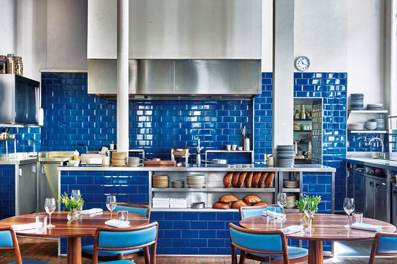 Cool ανοιχτή κουζίνα που ανεβάζει με  ζωηρό κοντράστ την ατμόσφαιρα στη λιτή σάλα του «The Clove Club»