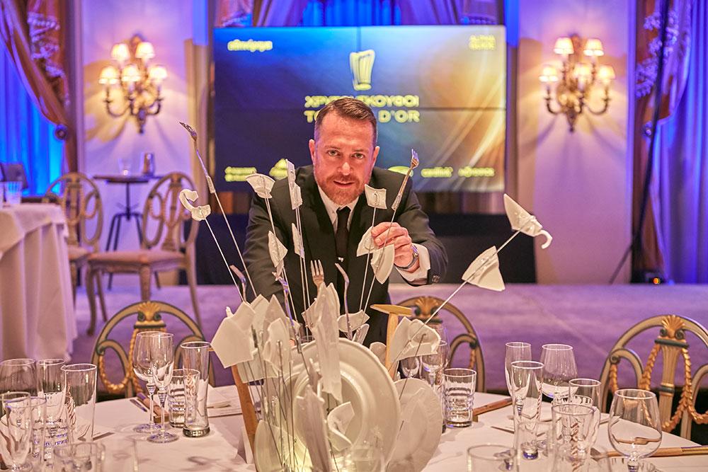 Ο Δημήτρης Μπραζάς δημιούργησε το εντυπωσιακό centerpiece της art de la table με θρυμματισμένα πιάτα και μαχαιροπίρουνα να ξεφυτρώνουν καταμεσής του τραπεζιού