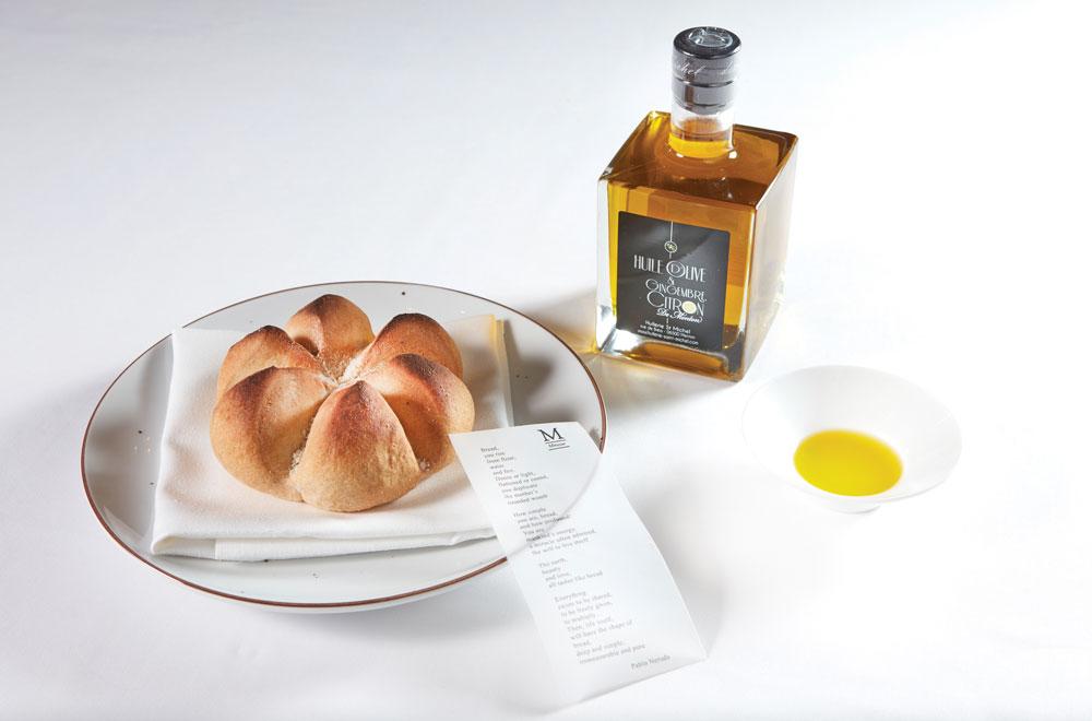 Το «ψωμί της μοιρασιάς», σερβιρισμένο με το ποίημα του Πάμπλο Νερούδα «Ωδή στο ψωμί», και το εξαιρετικό ελαιόλαδο του Mauro Colagreco με τζίντζερ και λεμόνι της Μεντόν.