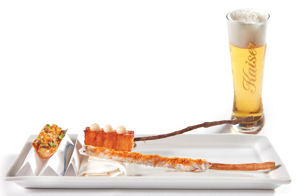 Μεσογειακό τσιπς ρεβιθιού με μελιτζάνα, αντζούγια, αβγοτάραχο, μιλφέιγ από μελωμένες πατάτες με τρούφα, στικ αποξηραμένου λαγόχορτου με lardo di Colonnata και μέλι σε δυναμική αρμονία με Kaiser Pilsner.